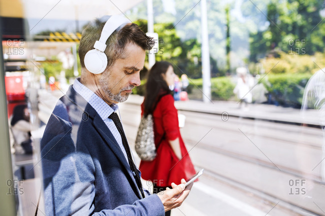 Businessman with smartphone and headphones waiting at the bus stop