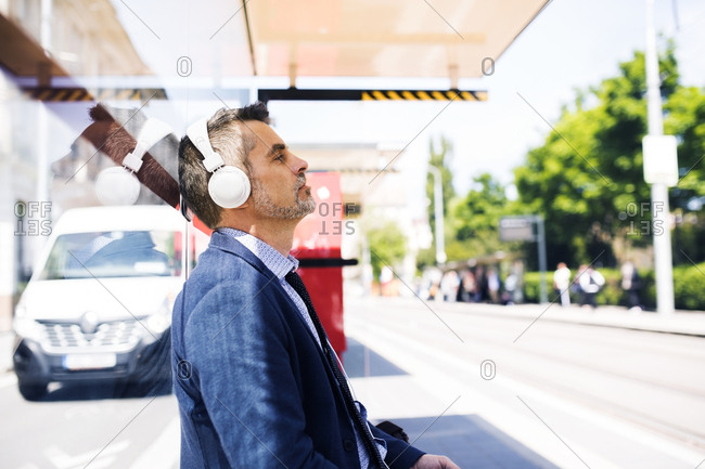 Businessman with headphones waiting at the bus stop