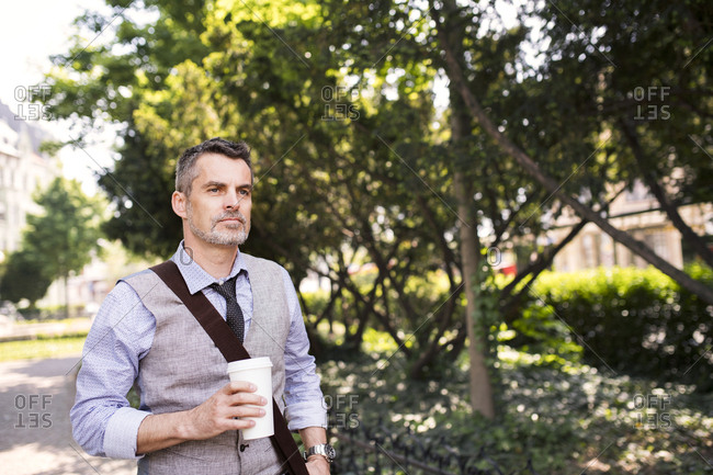 Mature businessman with coffee in city park
