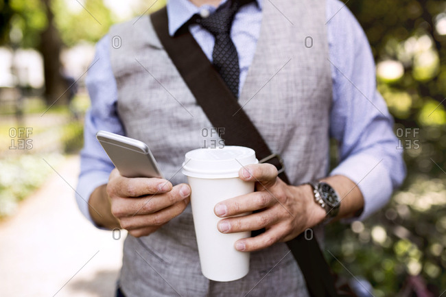 Close-up of businessman with coffee and smartphone in city park