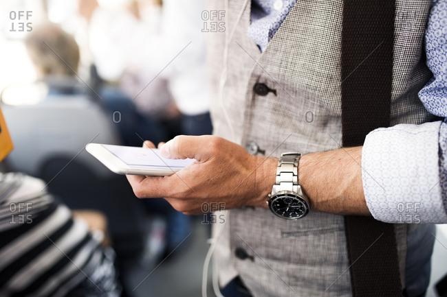 Close-up of businessman using smartphone in tram