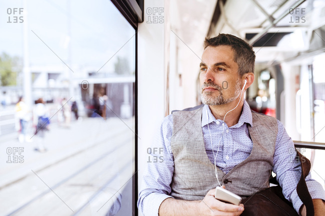 Businessman with smartphone and earphones travelling in tram
