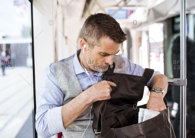 Businessman with earphones and bag travelling in tram