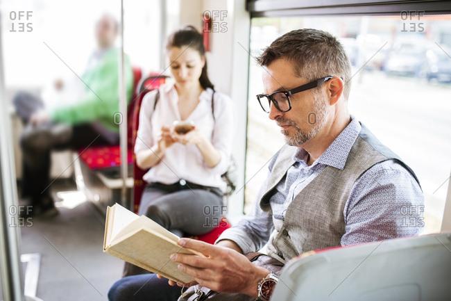 Businessman in tram reading book