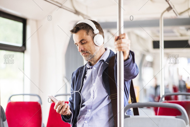 Businessman with smartphone and headphones travelling by bus