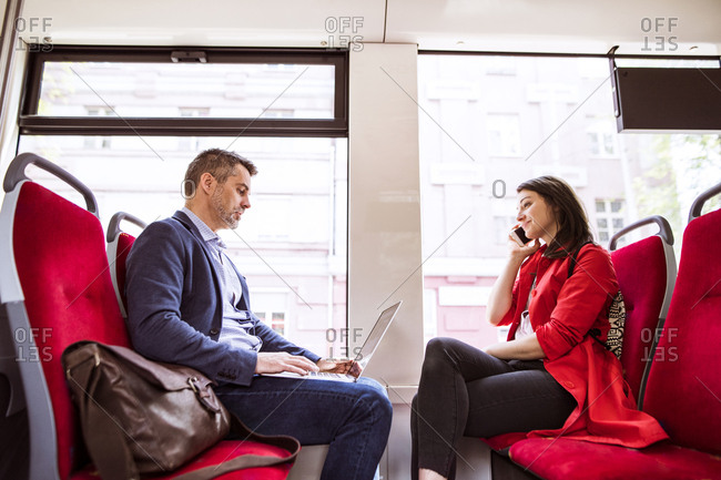 Businessman and woman with laptop and smartphone in bus