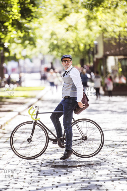 Mature businessman on bicycle in the city