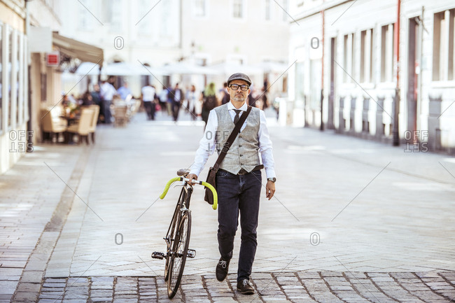 Mature businessman pushing bicycle in the city