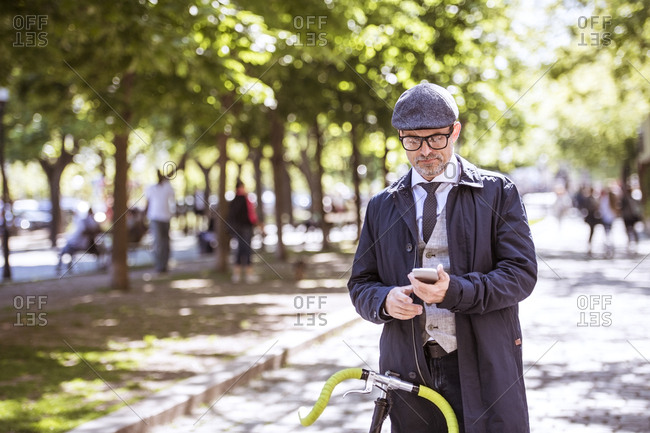 Mature businessman with bicycle and smartphone in the city