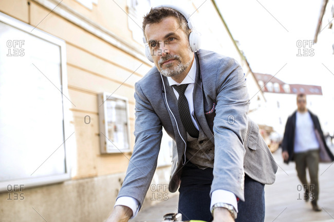 Mature businessman with headphones riding bicycle in the city