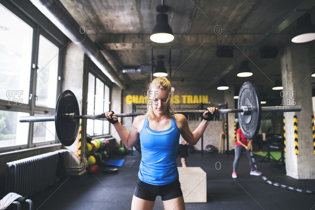 Young woman lifting barbell in gym
