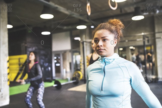Young woman with training partners exercising in gym
