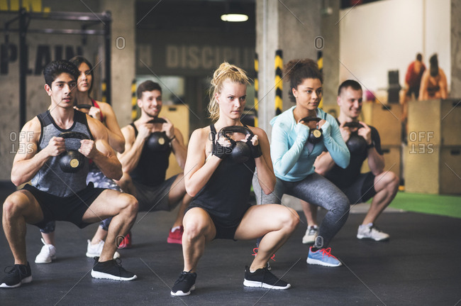 Group of young fit people lifting kettlebells in gym