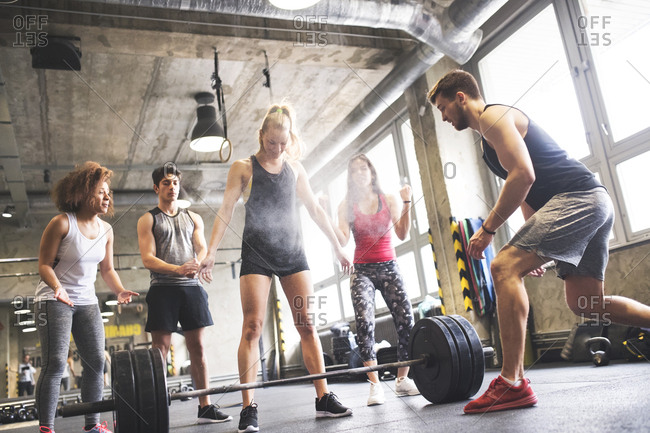 Group of young fit people cheering at woman weightlifting in gym