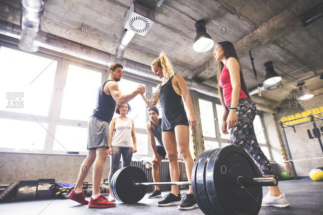 Group of young fit people motivating woman weightlifting in gym