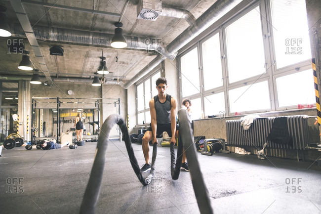Young athlete exercising with ropes in gym