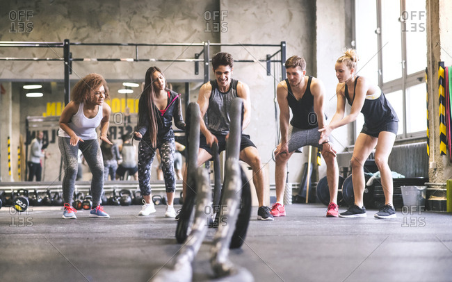 Group of young fit people cheering at man exercising with ropes in gym