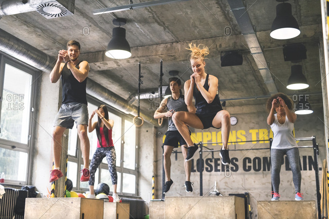 Group of young fit people doing box jumps in gym