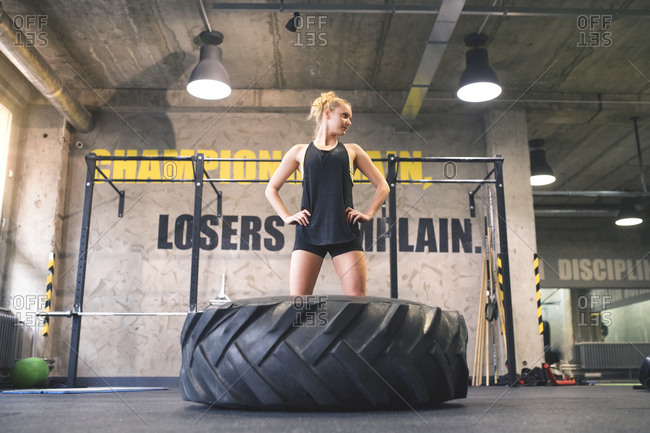 Young woman exercising with tractor tire in gym