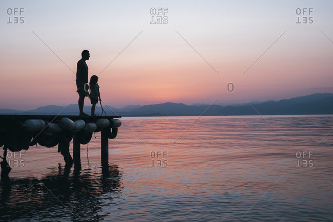 Italy- Lazise- father and little daughter standing on jetty looking at Lake Garda at sunset
