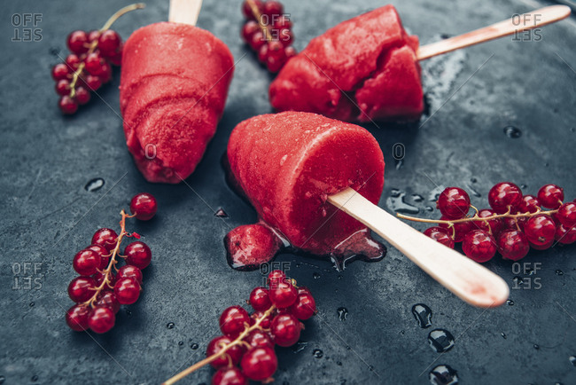 Homemade currant popsicles and red currants on slate
