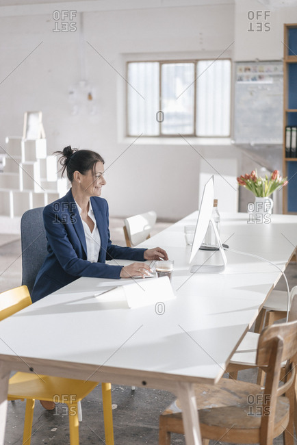 Businesswoman working at desk in a loft