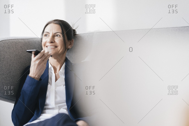 Portrait of smiling businesswoman sitting on couch using cell phone