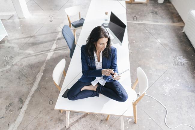 Businesswoman sitting on desk in a loft using tablet