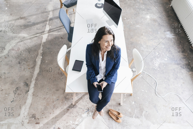 Smiling businesswoman sitting on desk in a loft