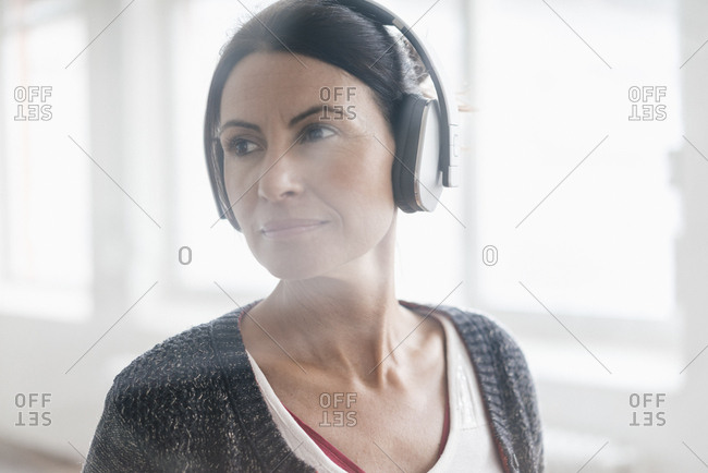 Portrait of woman listening music with headphones