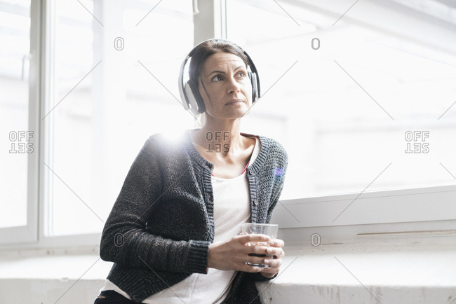 Portrait of woman in a loft listening music with headphones