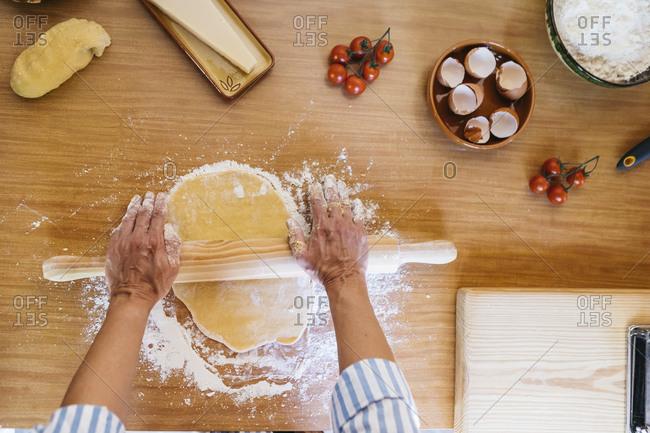 Woman preparing dough for ravioli- top view