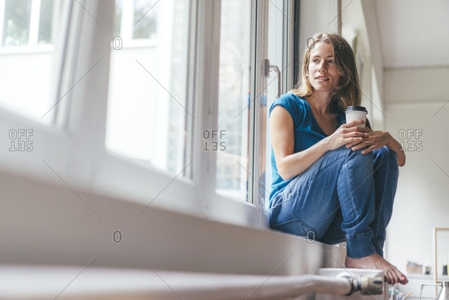 Smiling young woman holding takeaway coffee sitting at the window