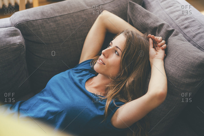 Relaxed young woman lying on couch at home
