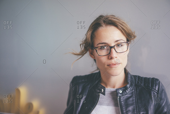 Portrait of young woman with glasses and leather jacket
