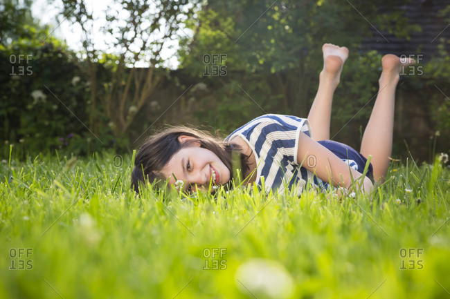 Portrait of smiling girl lying on a meadow in summer