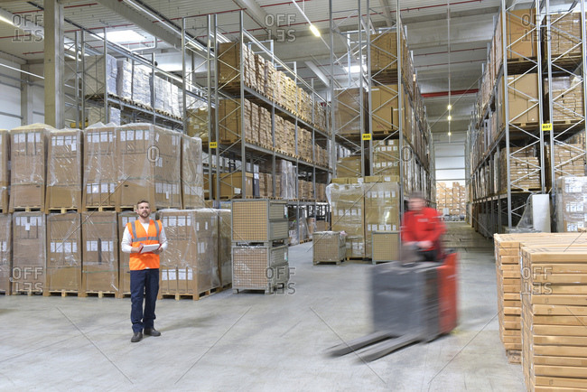 Man in factory hall and moving forklift