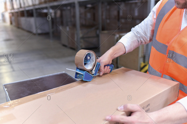 Man in factory hall wearing safety vest closing cardboard box
