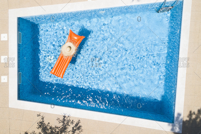 Straw hat on orange airbed in swimming pool- top view