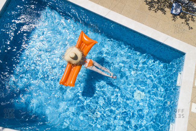 Back view of woman relaxing on orange airbed in swimming pool