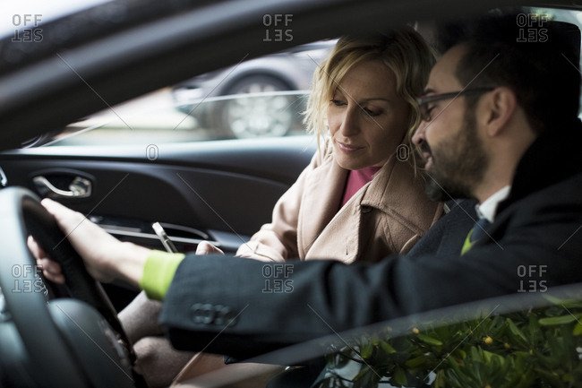 Businessman and businesswoman in car
