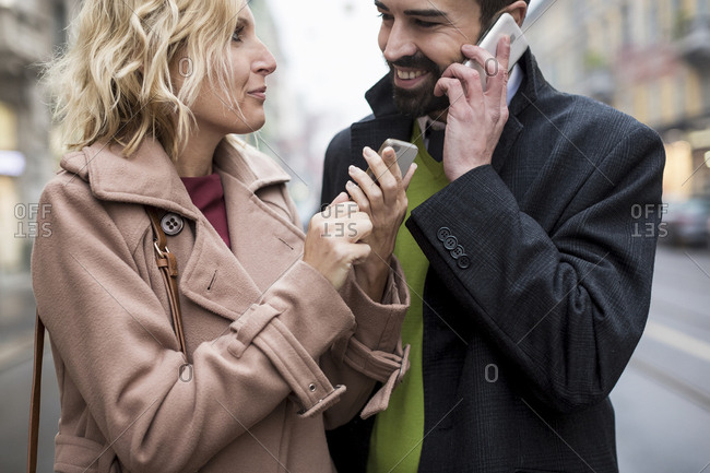 Happy business couple with cell phones in the city