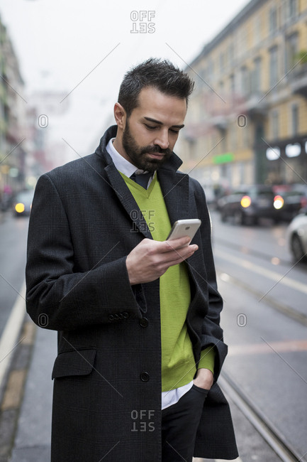 Businessman in the city checking cell phone