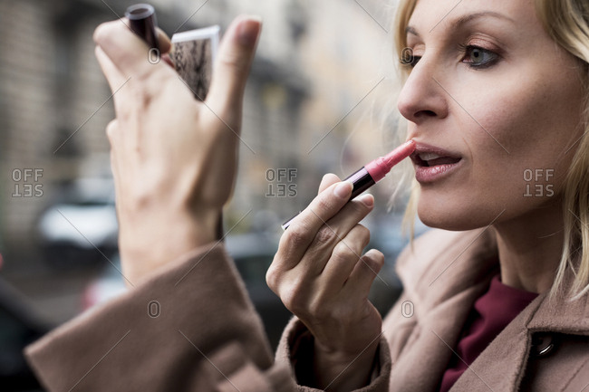 Businesswoman applying lipstick outdoors