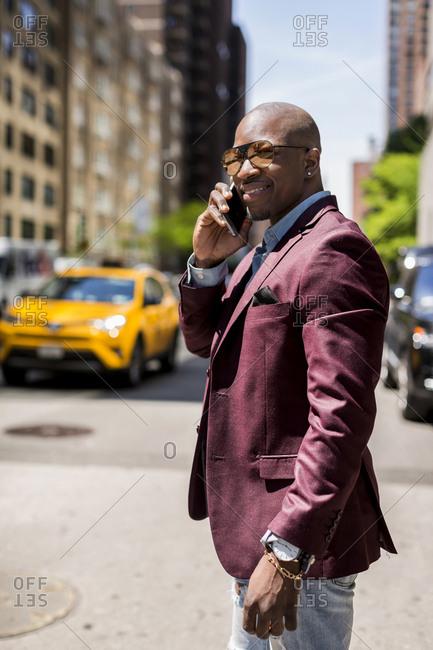 USA- New York City- Manhattan- portrait of smiling businessman on the phone