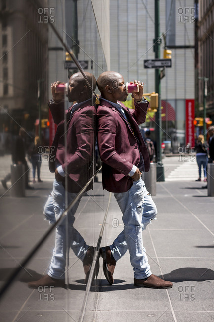 USA- New York City- Manhattan- stylish businessman with coffee to go leaning against glass facade