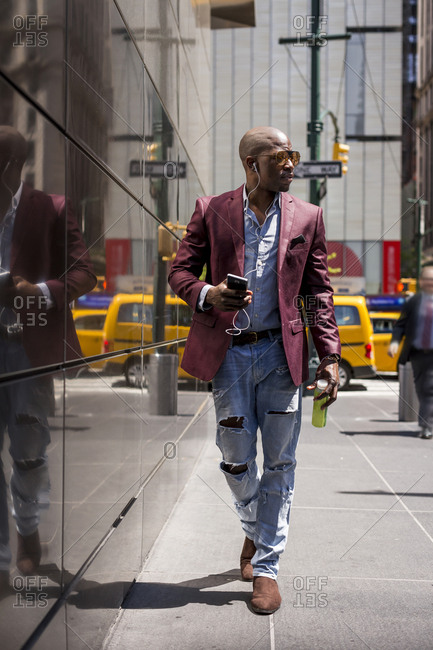 USA- New York City- Manhattan- stylish businessman listening music with headphones and smartphone