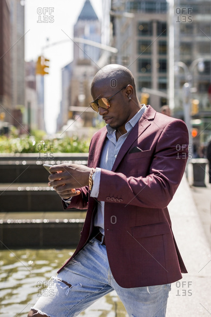 USA- New York City- Manhattan- stylish businessman looking at smartphone