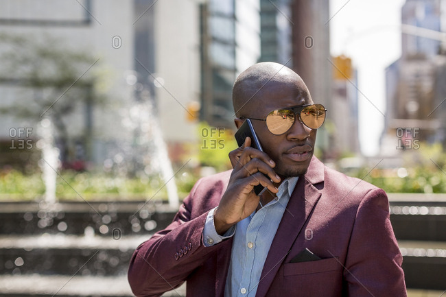 USA- New York City- Manhattan- portrait of businessman wearing mirrored sunglasses on the phone