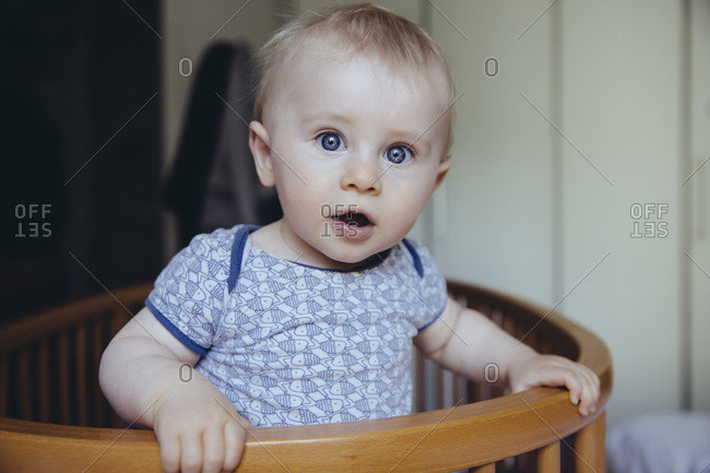 Portrait of baby boy standing in his crib